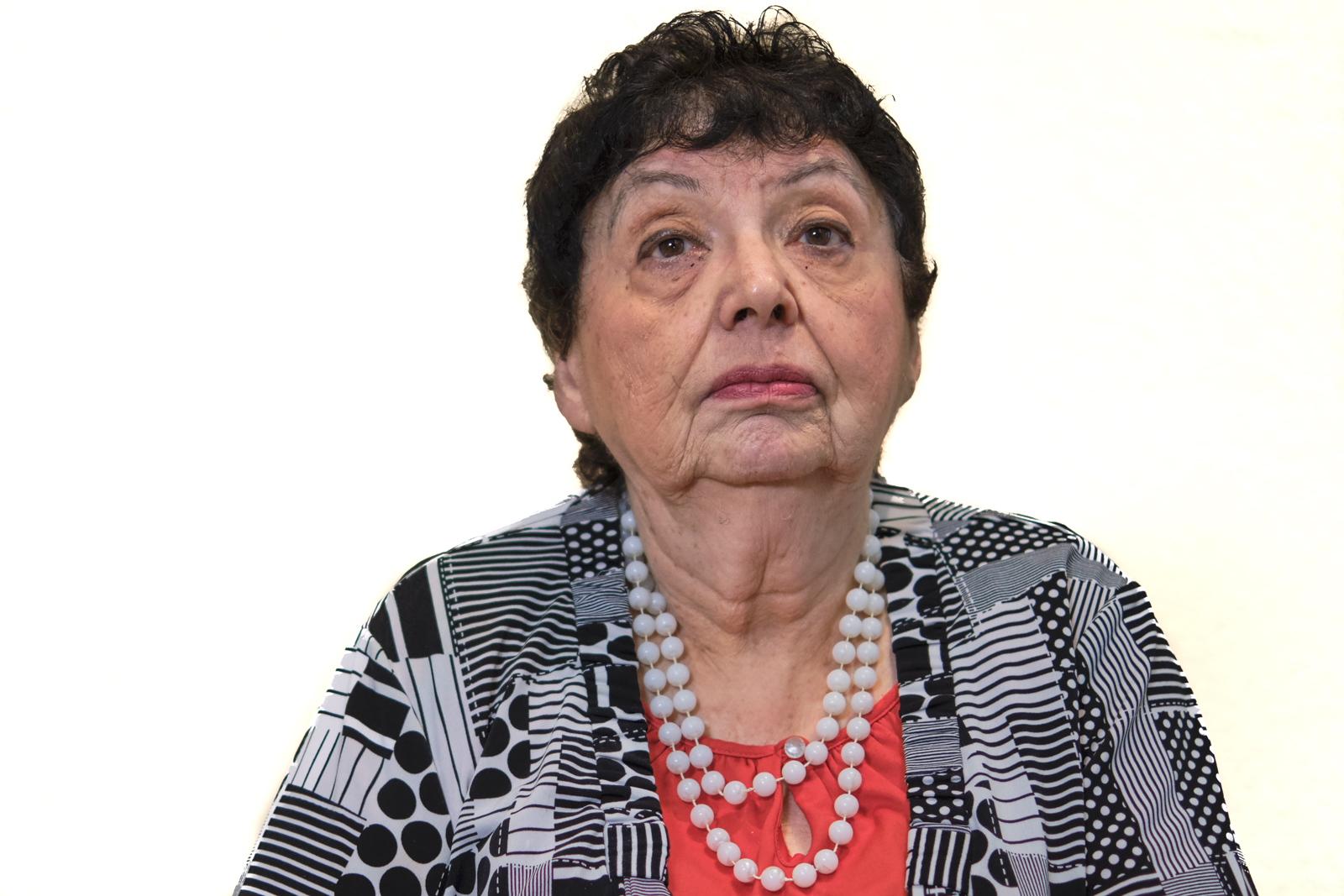 Porträt: Nachdenkliche, ältere Dame mit dunklen Haaren roter Bluse und schwer-weißem Blouson