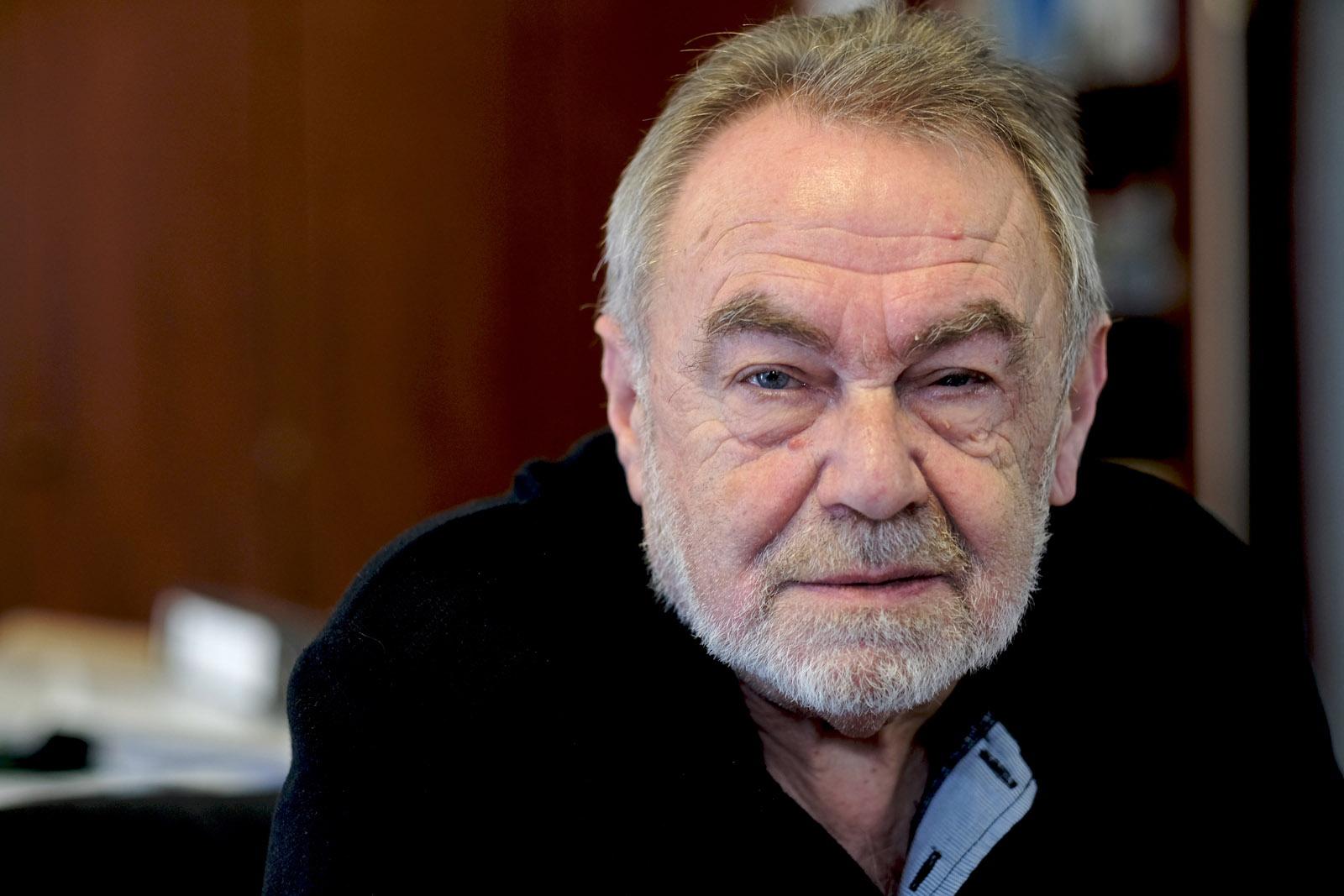 Porträt: Älterer Herr mit kurzem Vollbart, kurzem Haar und hoher Stirn.