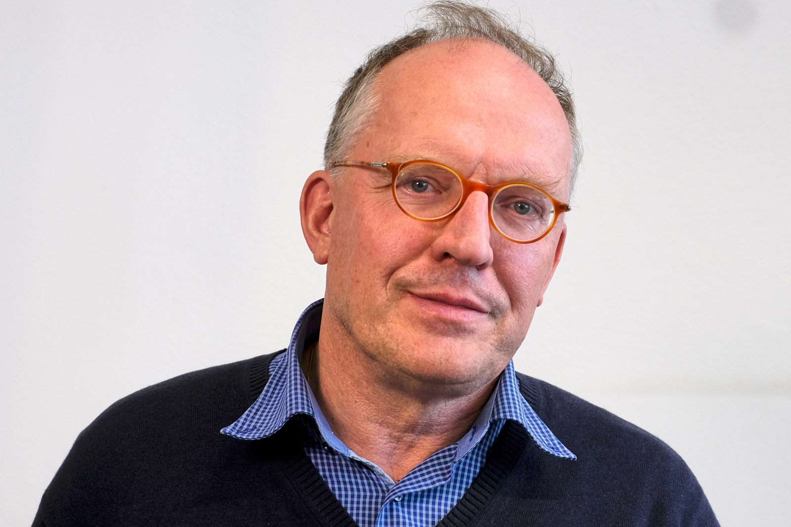 Porträt: Mann mittleren Alters mit sehr kurzen Haaren und roter Brille. Trägt ein blaues Hemd und eine schwarze Strickjacke